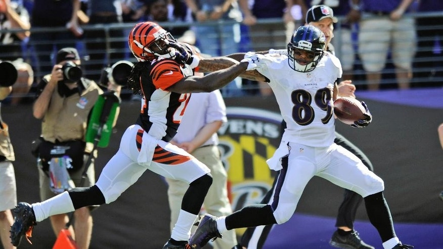 Baltimore Ravens wide receiver Steve Smith (89) stiff arms Cincinnati Bengals cornerback Adam Jones (24) as he runs for an 80 yard touchdown during the second half of an NFL football game in Baltimore, Md., Sunday, Sept. 7, 2014. Cincinnati Bengals defeated the Baltimore Ravens 23-16. (AP Photo/Gail Burton)