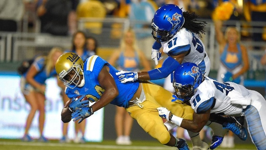 UCLA running back Paul Perkins, left, scores a touchdown as Memphis defensive backs Bakari Hollier, upper right, and Reggis Ball defend during the first half of an NCAA college football game, Saturday, Sept. 6, 2014, in Pasadena, Calif. (AP Photo/Mark J. Terrill)