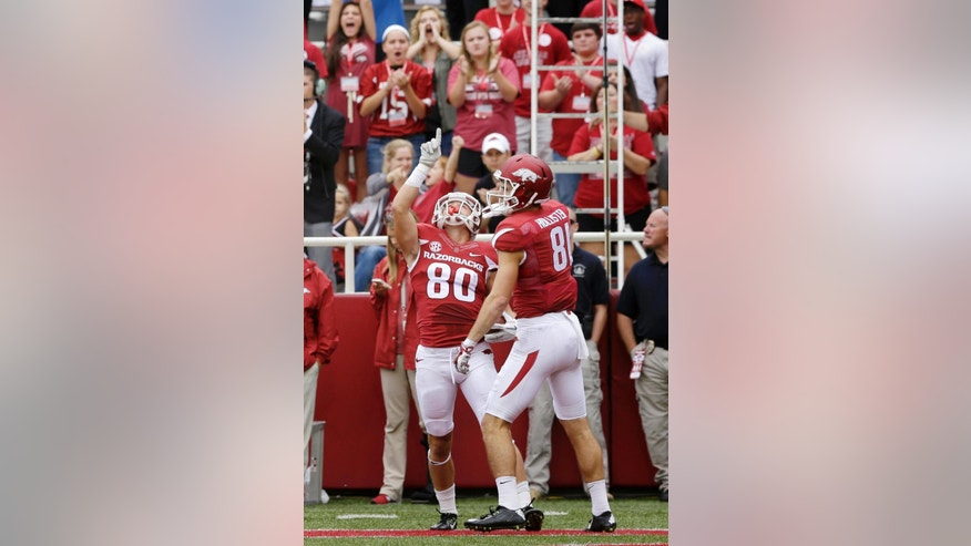 Arkansas wide receiver Drew Morgan (80) celebrates his first quarter touchdown with teammate wide receiver Cody Hollister (81) in an NCAA college football game against Nicholls State in Fayetteville, Ark., Saturday, Sept. 6, 2014. (AP Photo/Danny Johnston)