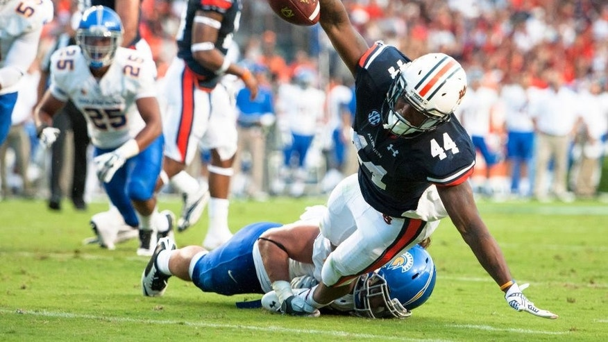 Auburn running back Cameron Artis-Payne (44) dives for a touchdown as San Jose State linebacker Christian Tago (4) grabs his legs during an NCAA football game, Saturday, Sept. 6, 2014, at Jordan-Hare Stadium in Auburn, Ala.(AP Photo/The Montgomery Advertiser, Albert Cesare)  NO SALES
