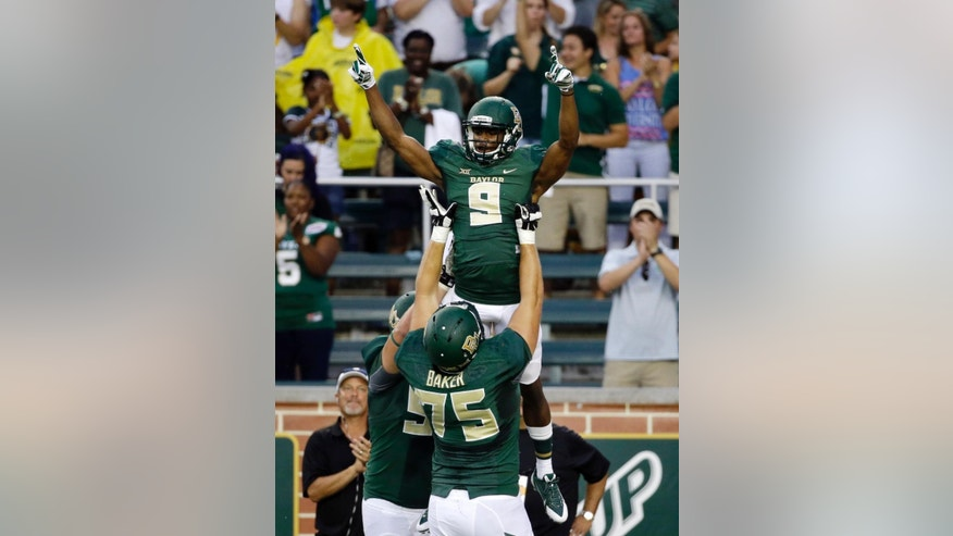 Baylor wide receiver KD Cannon (9) is lifted by Troy Baker (75) after a reception and touchdown score by Cannon in the first half of an NCAA college football game against Northwestern State, Saturday, Sept. 6, 2014, in Waco, Texas. (AP Photo/Tony Gutierrez)