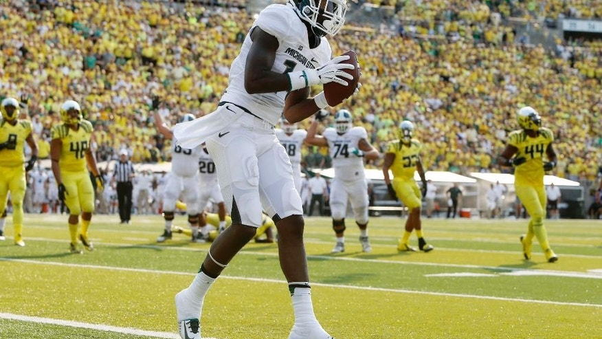Michigan State's Tony Lippett comes down with a touchdown reception against Oregon during the second quarter of their college football game in Eugene, Oregon, Saturday Sept. 6, 2014. (AP Photo/Chris Pietsch)