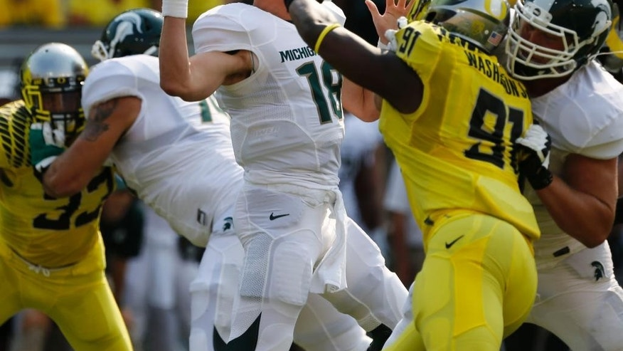 Michigan State quarterback Connor Cook, left, passes down field under pressure from Oregon's Tony Washington during the first quarter of their college football game in Eugene, Oregon, Saturday Sept. 6, 2014. (AP Photo/Chris Pietsch)