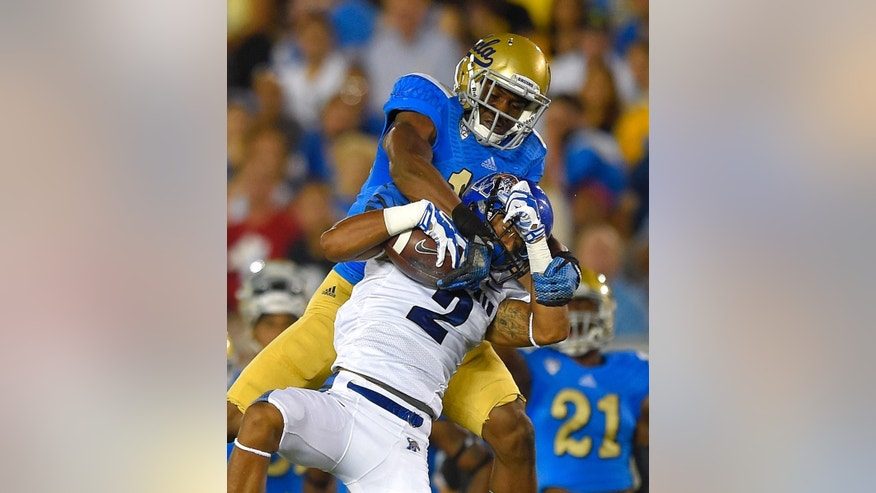 Memphis wide receiver Joe Craig, below, makes a catch as UCLA defensive back Fabian Moreau tackles him during the first half of an NCAA college football game, Saturday, Sept. 6, 2014, in Pasadena, Calif. (AP Photo/Mark J. Terrill)