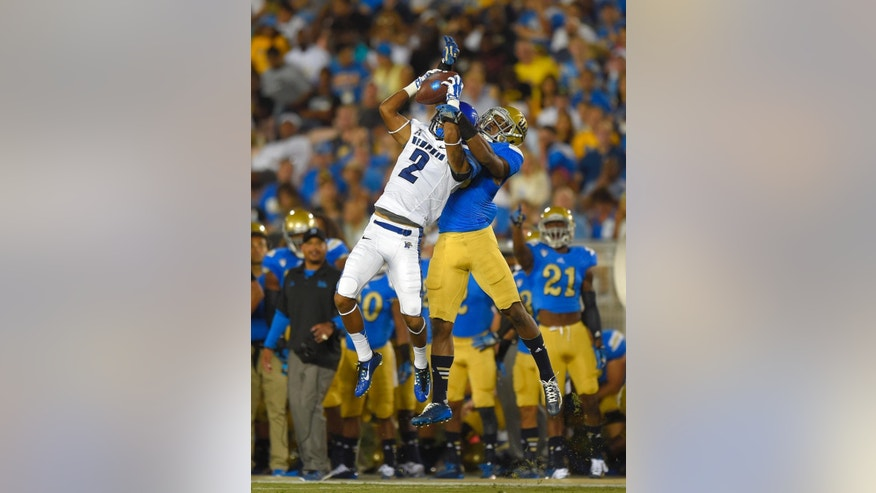 Memphis wide receiver Joe Craig, left, makes a catch as UCLA defensive back Fabian Moreau goes up for the ball with him during the first half of an NCAA college football game, Saturday, Sept. 6, 2014, in Pasadena, Calif. (AP Photo/Mark J. Terrill)