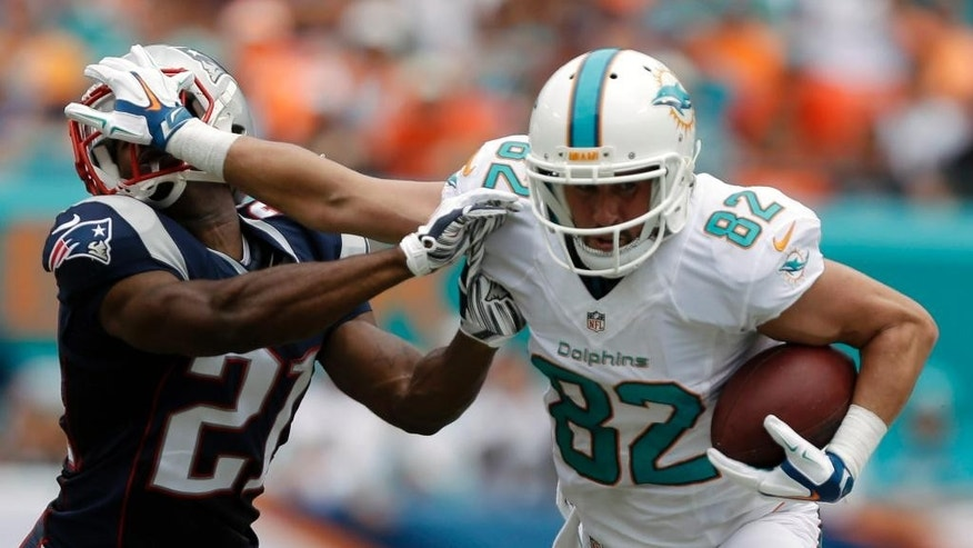 Miami Dolphins wide receiver Brian Hartline (82) defends against a tackle by New England Patriots cornerback Malcolm Butler (21), during the first half of an NFL football game in Miami Gardens, Fla., Sunday, Sept. 7, 2014. (AP Photo/Lynne Sladky)