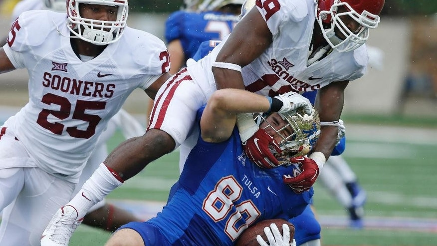 Oklahoma linebacker Eric Striker (19) tackles Tulsa wide receiver Conner Floyd (80) in the fourth quarter of an NCAA college football game in Tulsa, Okla., Saturday, Sept. 6, 2014. Oklahoma won 52-7. (AP Photo/Sue Ogrocki)
