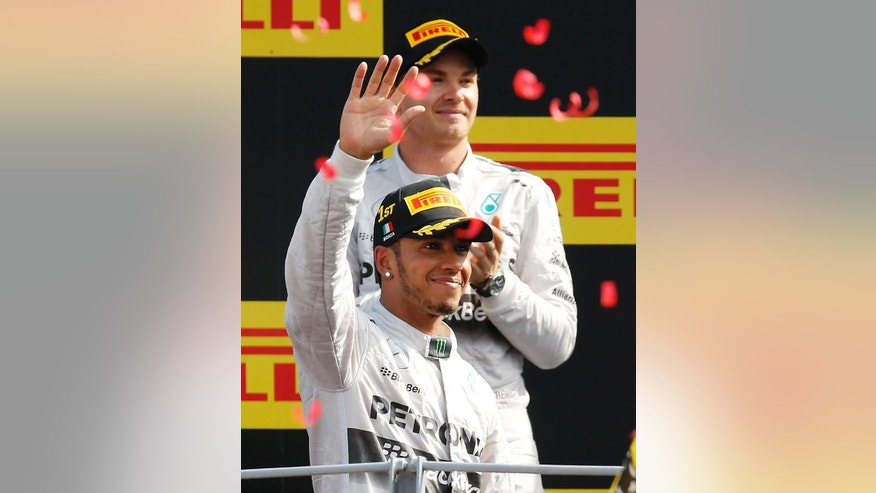 Mercedes driver Lewis Hamilton, foreground, of Britain, celebrates on the podium with second placed Mercedes driver Nico Rosberg, of Germany, after winning the Italian Formula One Grand Prix at the Monza racetrack, in Monza, Italy, Sunday, Sept. 7, 2014. (AP Photo/Antonio Calanni)