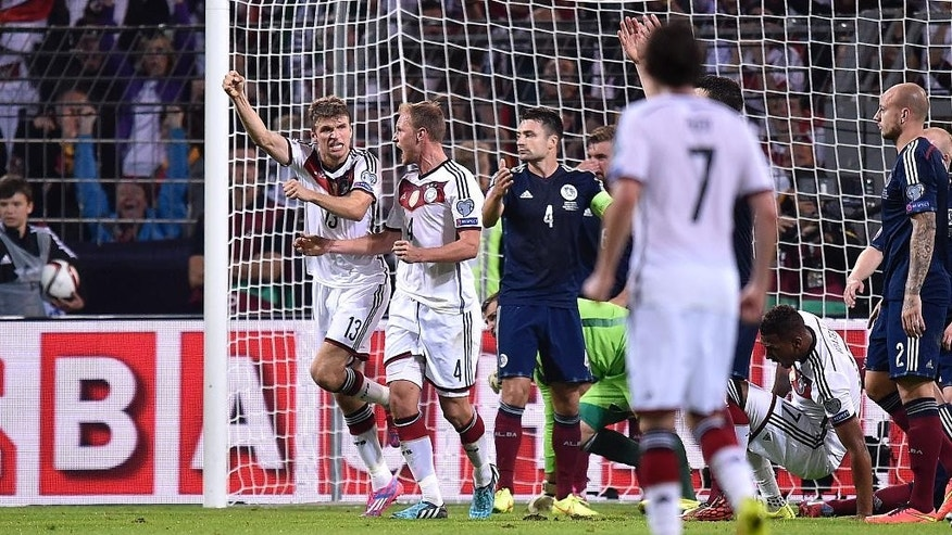 Germany's Thomas Mueller, left, celebrates after scoring his second goal during the Euro 2016 soccer qualifying group D match between Germany and Scotland in Dortmund, Germany, Sunday, Sept. 7, 2014. (AP Photo/Martin Meissner)