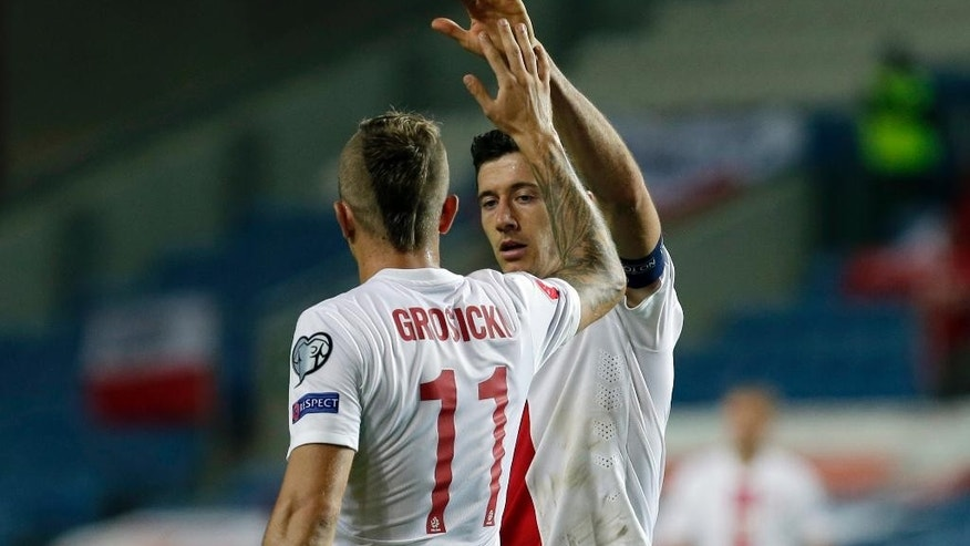 Poland's Robert Lewandowski, right, celebrates with teammate Kamil Grosicki after scoring their side's fourth goal against Gibraltar during an Euro2016 Group D qualifying round soccer match between Gibraltar and Poland at the Algarve stadium in Faro, southern Portugal, Sunday, Sept. 7, 2014. (AP Photo/Francisco Seco)