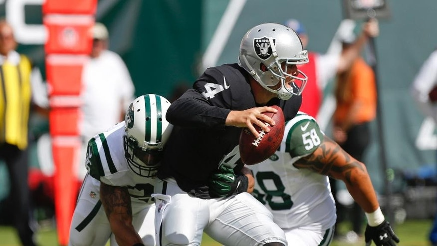 Oakland Raiders quarterback Derek Carr (4) looks to pass as he is sacked by New York Jets' Dawan Landry (26) during the second half of an NFL football game Sunday, Sept. 7, 2014, in East Rutherford, N.J. (AP Photo/Seth Wenig)