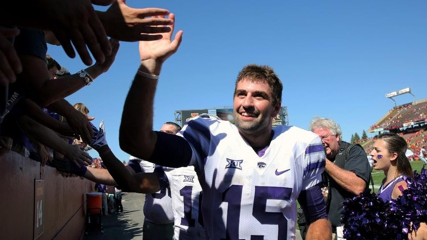 Kansas State quarterback Jake Waters (15) gets high fives from fans after their 32-28 win over Iowa State in an NCAA college football game Saturday, Sept. 6, 2014, in Ames, Iowa. (AP Photo/Justin Hayworth)