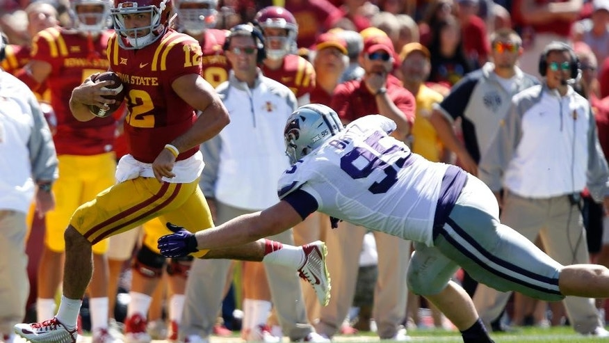 Iowa State quarterback Sam B. Richardson (12) runs from diving Kansas State defensive lineman Travis Britz (95) during the second half of an NCAA college football game Saturday, Sept. 6, 2014, in Ames, Iowa. Kansas State won 32-28. (AP Photo/Justin Hayworth)
