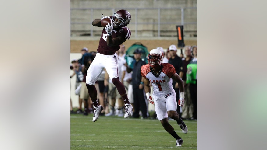 Texas A&M wide receiver Speedy Noil (2) catches a pass for a first down as Lamar running back Carl Harris (1) defends during the first quarter of an NCAA college football game Saturday, Sept. 6, 2014, in College Station, Texas. (AP Photo/David J. Phillip)