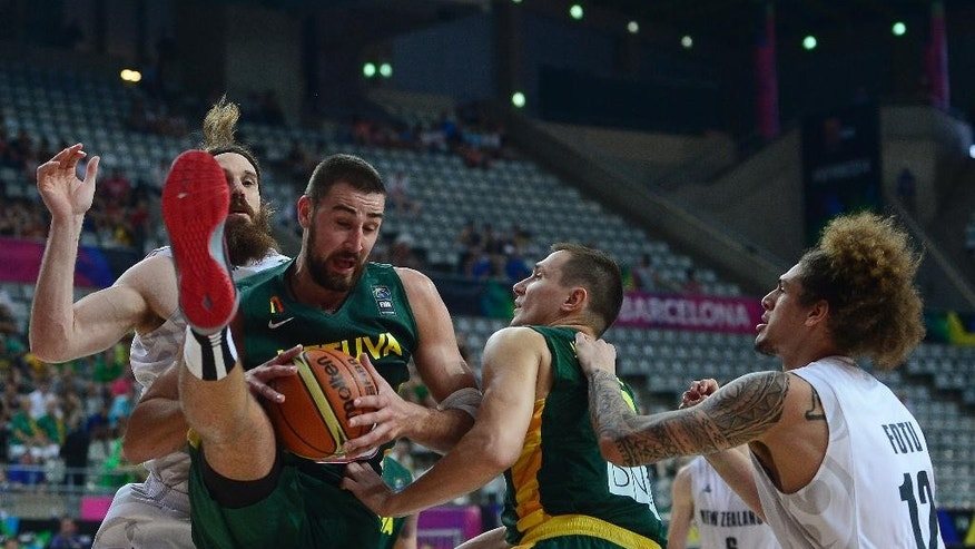 New Zealand's Casey Frank, left, vies for the ball over Lithuania's Jonas Valanciunas, second left, during Basketball World Cup Round of 16 match between New Zealand and Lithuania at the Palau Sant Jordi in Barcelona, Spain, Sunday, Sept. 7, 2014. The 2014 Basketball World Cup competition will take place in various cities in Spain from Aug. 30 through to Sept. 14. (AP Photo/Manu Fernandez)