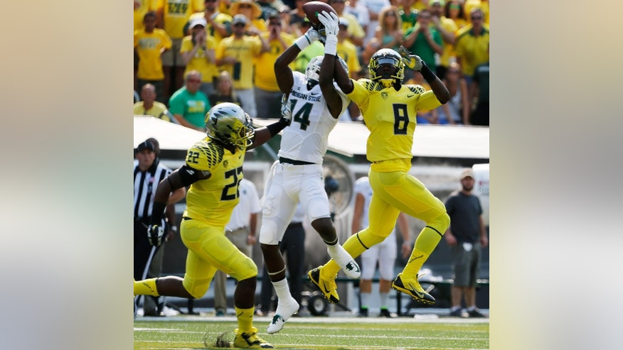 CORRECTS NAME OF MICHIGAN PLAYER TO TONY LIPPETT - Oregon's Derrick Malone Jr., left, and Reggie Daniels, right, double team Michigan State's Chris Laneaux, center, to force an incomplete pass during the first quarter of their  NCAA college football game in Eugene, Oregon, Saturday Sept. 6, 2014. (AP Photo/Chris Pietsch)