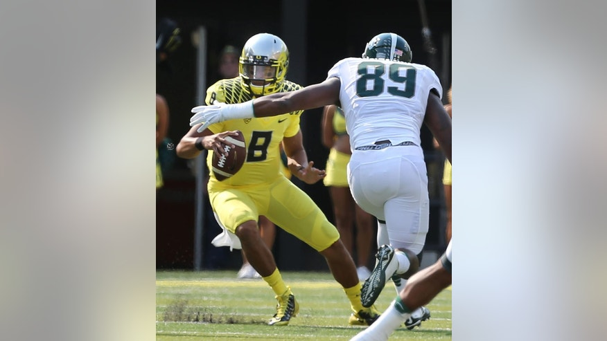 Oregon quarterback Marcus Mariota, left, is flushed out of the pocket by Michigan State's Shilique Calhoun during the first quarter of their college football game in Eugene, Oregon, Saturday Sept. 6, 2014. (AP Photo/Chris Pietsch)