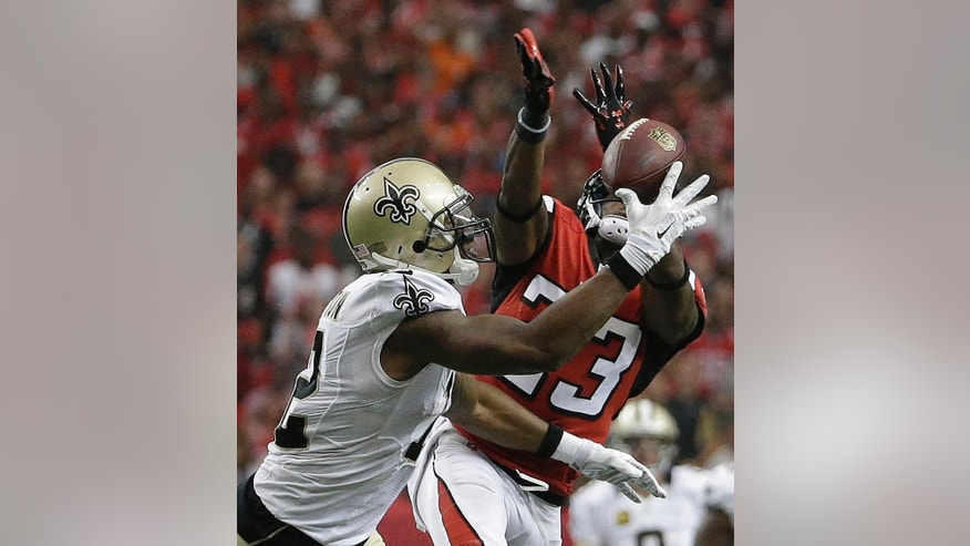 New Orleans Saints wide receiver Marques Colston (12) and Atlanta Falcons cornerback Robert Alford (23) vie for a passed ball during the second half of an NFL football game, Sunday, Sept. 7, 2014, in Atlanta. Alford was charged with a penalty. (AP Photo/David Goldman)