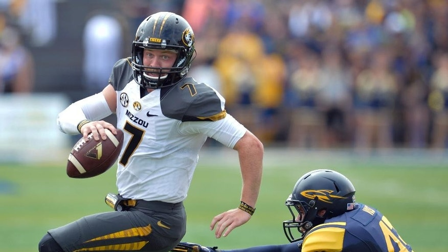 Missouri quarterback Maty Mauk (7) scrambles from Toledo linebacker Trent Voss (43) in the first quarter of an NCAA college football game in Toledo, Ohio, Saturday, Sept. 6, 2014. (AP Photo/David Richard)