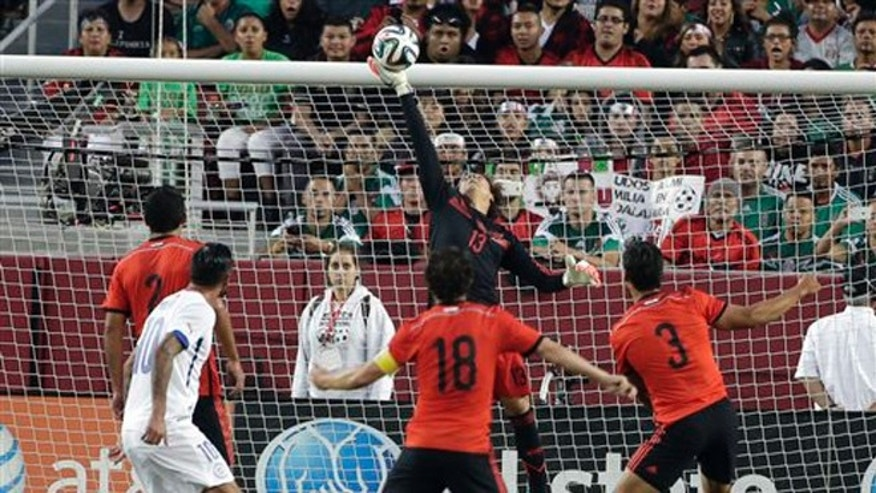 Mexico goalkeeper Guillermo Ochoa, center, makes a save against Chile during the first half of an international friendly soccer match on Saturday, Sept. 6, 2014, in Santa Clara, Calif. (AP Photo/Marcio Jose Sanchez)