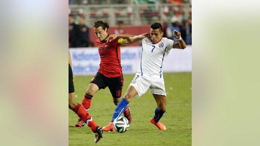 Mexico's Andres Guardado, left, battles against Chile's Alexis Sanchez during the second half of an international friendly soccer match on Saturday, Sept. 6, 2014, in Santa Clara, Calif. The game ended in a 0-0 draw. (AP Photo/Marcio Jose Sanchez)