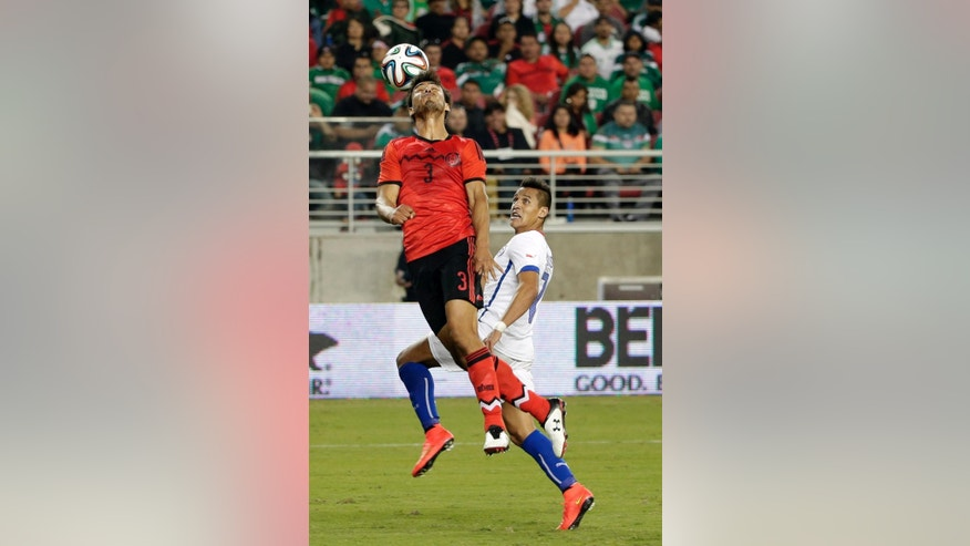 Mexico's Oswaldo Alanis (3) heads the ball next to Chile's Alexis Sanchez during the second half of an international friendly soccer match Saturday, Sept. 6, 2014, in Santa Clara, Calif. The game ended in a 0-0 draw. (AP Photo/Marcio Jose Sanchez)