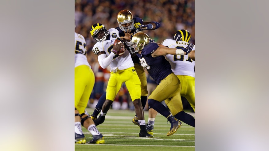 Michigan quarterback Devin Gardner, left, is pressured by Notre Dame defensive lineman Andrew Trumbetti, right, and Jarron Jones during the second half of an NCAA college football game in South Bend, Ind., Saturday, Sept. 6, 2014. (AP Photo/Michael Conroy)