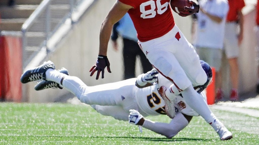 Wisconsin's Alex Erickson gets past Western Illinois's David McDaniel (22) after a catch during the second half of an NCAA college football game Saturday, Sept. 6, 2014, in Madison, Wis. Wisconsin won 37-3. (AP Photo/Morry Gash)