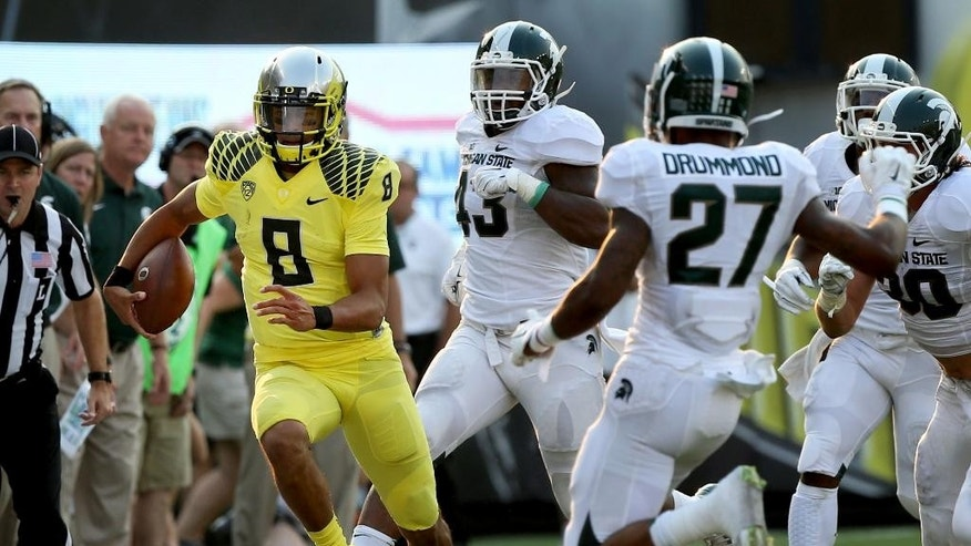 Oregon quarterback Marcus Mariota, left, runs down the sidelines ahead of a host of Michigan State defenders during the 3rd quarter of their NCAA college football game in Eugene, Oregon, Saturday Sept. 6, 2014. (AP Photo/Chris Pietsch)