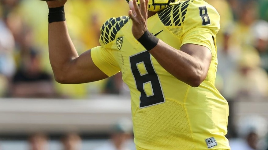 Oregon's Marcus Mariota passes down field against  Michigan State during the 2nd quarter of their college football game in Eugene, Ore. Saturday Sept. 6, 2014. (AP Photo/Chris Pietsch)