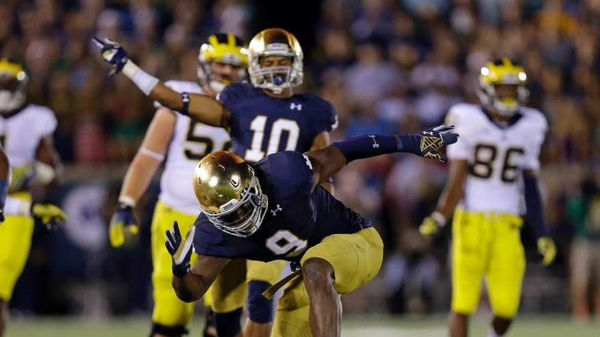 Notre Dame linebacker Jaylon Smith celebrates a tackle for a loss against Michigan during the second half of an NCAA college football game in South Bend, Ind., Saturday, Sept. 6, 2014. (AP Photo/Michael Conroy)