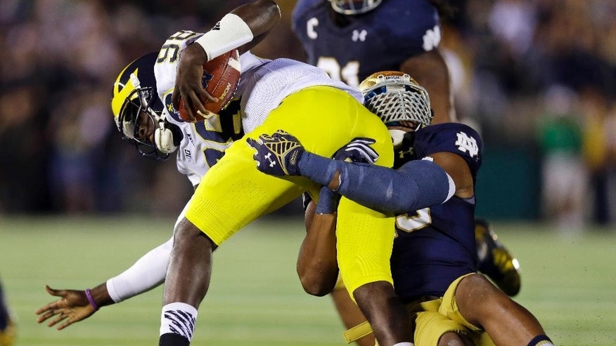 Michigan quarterback Devin Gardner is sacked by Notre Dame defensive lineman Romeo Okwara, right, during the first half of an NCAA college football game in South Bend, Ind., Saturday, Sept. 6, 2014. (AP Photo/Michael Conroy)