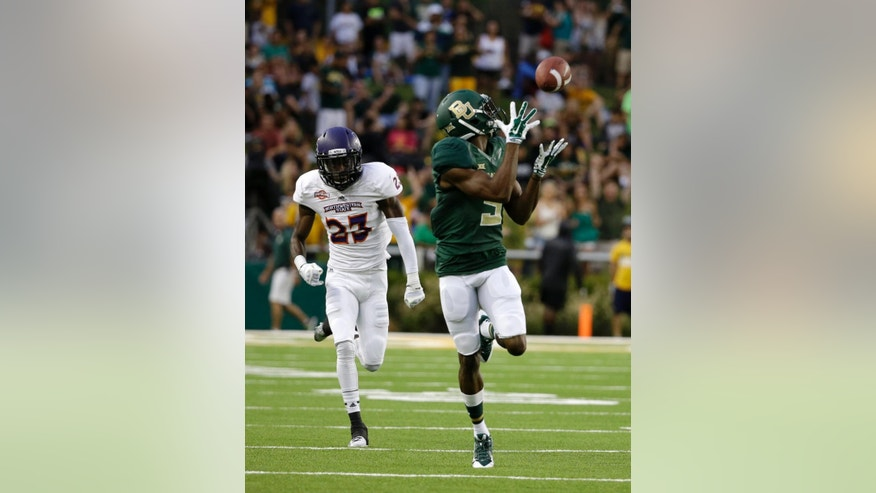 Baylor wide receiver KD Cannon reaches up to grab a pass as Northwestern State cornerback Fred Thomas (23) defends in the first half of an NCAA college football game, Saturday, Sept. 6, 2014, in Waco, Texas. Cannon sprinted to the end zone for at touchdown on a the play. (AP Photo/Tony Gutierrez)