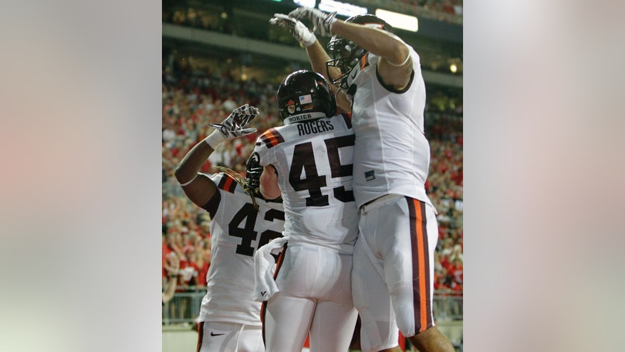 Virginia Tech fullback Sam Rogers (45) celebrates his touchdown against Ohio State with teammates Marshawn Williams, left, and Bucky Hodges during the second quarter of an NCAA college football game Saturday, Sept. 6, 2014, in Columbus, Ohio. (AP Photo/Jay LaPrete)