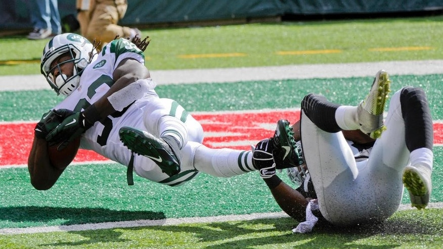 New York Jets running back Chris Ivory (33) dives away from Oakland Raiders' T.J. Carrie for a touchdown during the second half of an NFL football game Sunday, Sept. 7, 2014, in East Rutherford, N.J. (AP Photo/Bill Kostroun)