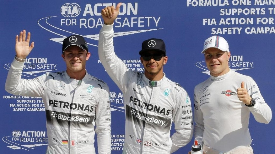 Mercedes driver Lewis Hamilton, center, of Britain, celebrates after setting the pole position with second placed Mercedes driver Nico Rosberg, left, of Germany, and third placed Williams driver Valtteri Bottas, of Finland, during the qualifying session at the Monza racetrack, in Monza, Italy, Saturday, Sept. 6, 2014. The Formula One race will be held on Sunday. (AP Photo/Antonio Calanni)