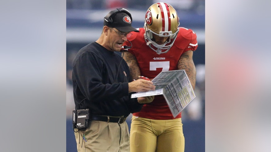 San Francisco 49ers head coach Jim Harbaugh, left, and San Francisco 49ers quarterback Colin Kaepernick (7) discuss plays in the first half of an NFL football game against the Dallas Cowboys, Sunday, Sept. 7, 2014, in Arlington, Texas. (AP Photo/LM Otero)