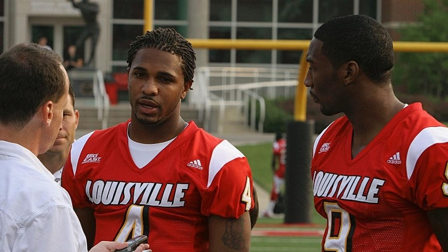 FILE - This Saturday, Aug. 6, 2005, file photo shows Christopher Duncan, left, interviewing University of Louisville senior wide receiver Broderick Clark, center, in Louisville, Ky. Duncan, a sports reporter for The Associated Press who joined the company in 1994 died Monday, Sept. 8, 2014 at the age of 43.  (AP Photo/Garry Jones, File)