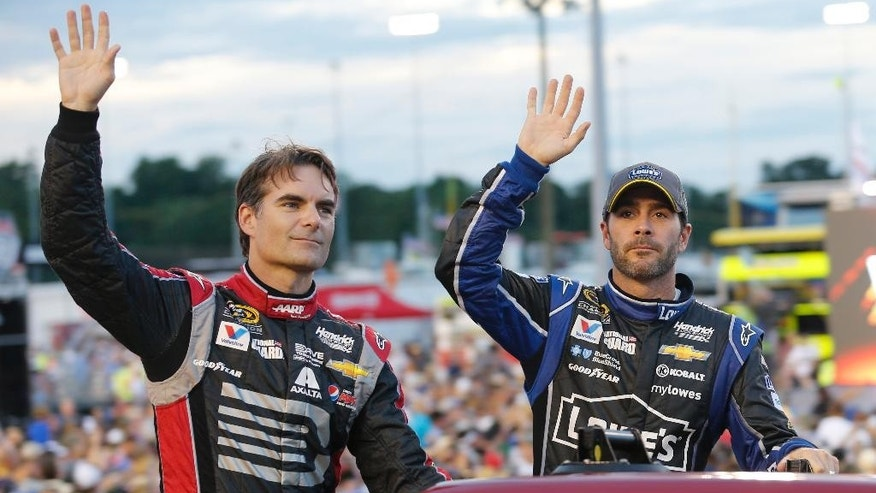 Jeff Gordon, left, and Jimmie Johnson wave to the crowd during driver introductions for the NASCAR Sprint Cup series auto race at Richmond International Raceway in Richmond, Va., Saturday, Sept. 6, 2014. (AP Photo/Steve Helber)
