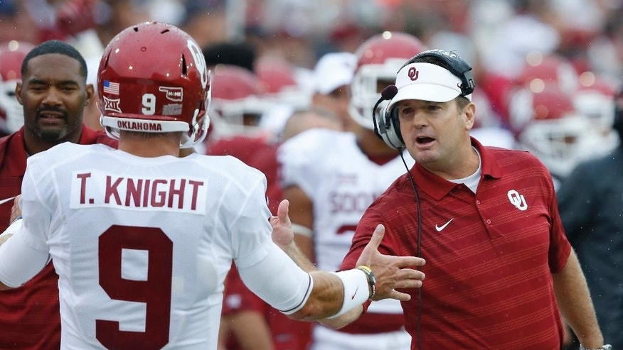 Oklahoma head coach Bob Stoops, right, greets quarterback Trevor Knight (9) as he returns to the bench following a touchdown by tight end Blake Bell in the first quarter of an NCAA college football game against Tulsa in Tulsa, Okla., Saturday, Sept. 6, 2014. (AP Photo/Sue Ogrocki)