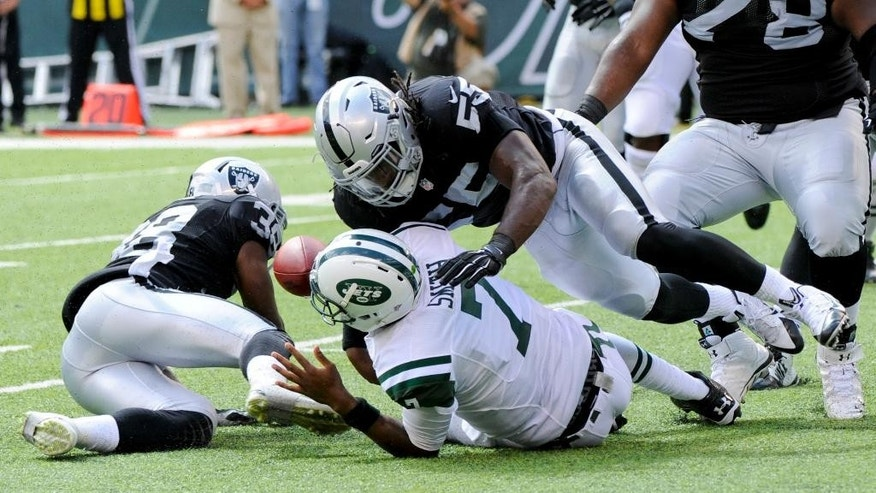 New York Jets' Geno Smith (7) fumbles the ball as he is hit by Oakland Raiders' Sio Moore (55) during the first half of an NFL football game Sunday, Sept. 7, 2014, in East Rutherford, N.J. (AP Photo/Bill Kostroun)