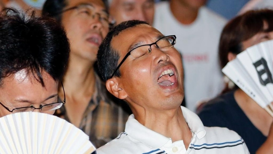 Supporters react as they watch on the television Japan's Kei Nishikori play Marin Cilic of Croatia at the U.S. Open tennis final, in Matsue, hometown of Nishikori, western Japan, Tuesday, Sept. 9, 2014. (AP Photo/Shizuo Kambayashi)