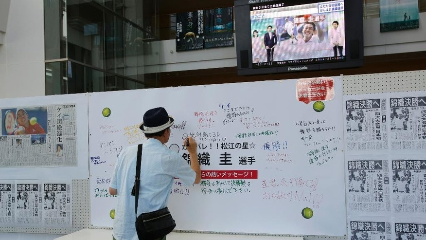 """A man writes a message to Japanese tennis player Kei Nishikori on a board with newspapers reporting him in the U.S. Open, in Nishikori's hometown of Matsue, western Japan, Monday, Sept. 8, 2014. Nishikori, the first man from Asia to make it to the final of a Grand Slam singles tournament, faces Marin Cilic in the U.S. Open men's final on Monday. The newspapers' headlines read: """"Nishikori advances to the final.""""  (AP Photo/Shizuo Kambayashi)"""