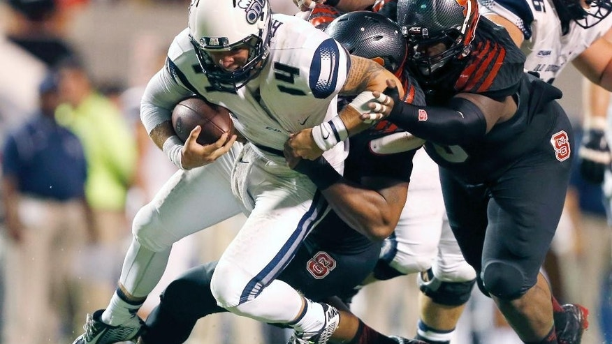 North Carolina State's Mike Rose (90) and T.Y. McGill (75), right, sack Old Dominion quarterback Taylor Heinicke (14) during an NCAA college football game at Carter-Finley Stadium in Raleigh, N.C., Saturday, Sept. 6, 2014. (AP Photo/The News & Observer, Ethan Hyman)  MANDATORY CREDIT