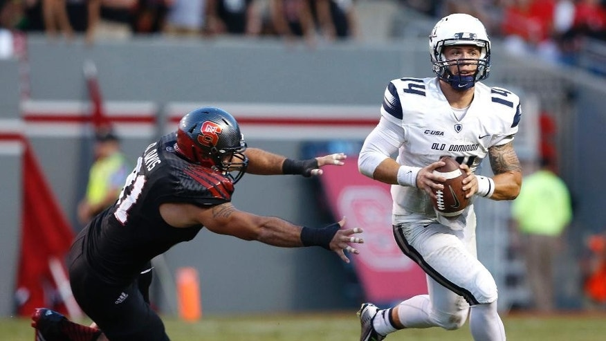 Old Dominion quarterback Taylor Heinicke (14) avoids the pressure of North Carolina State defensive end Drew Davis (91) during the first half of an NCAA college football game at Carter-Finley Stadium in Raleigh, N.C., Saturday, Sept. 6, 2014. (AP Photo/The News & Observer, Ethan Hyman) MANDATORY CREDIT