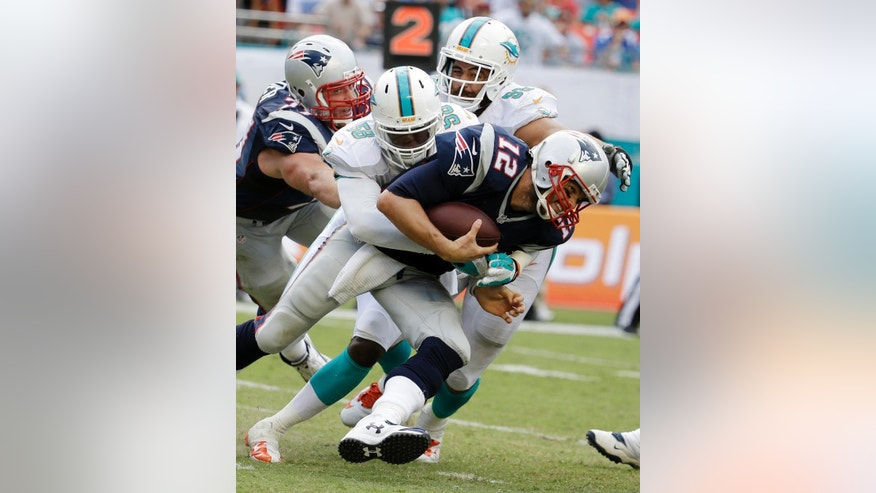 New England Patriots quarterback Tom Brady (12) is sacked by Miami Dolphins linebacker Chris McCain (58), during the second half of an NFL football game, in Miami Gardens, Fla., Sunday Sept. 7, 2014. (AP Photo/Lynne Sladky)