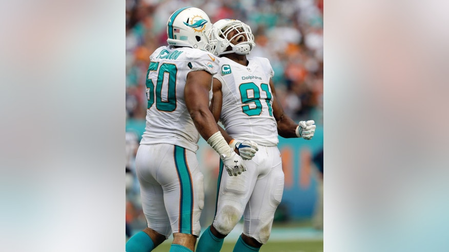 Miami Dolphins defensive end Cameron Wake (91) celebrates with defensive end Olivier Vernon (50) after sacking New England Patriots quarterback Tom Brady during the second half of an NFL football game in Miami Gardens, Fla., Sunday, Sept. 7, 2014. The sack led to a fumble recovered by the Dolphins. The Dolphins won 33-20. (AP Photo/Wilfredo Lee)
