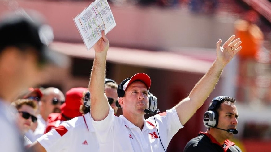 Nebraska head coach Bo Pelini, center, and defensive coordinator John Papuchis, right, react to a replay on the big screen, in the second half of an NCAA college football game against McNeese State in Lincoln, Neb., Saturday, Sept. 6, 2014. Nebraska won 31-24. (AP Photo/Nati Harnik)