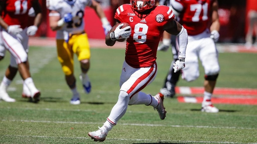 Nebraska running back Ameer Abdullah (8) runs for 58 yards for the winning touchdown against McNeese State with 20 seconds left in the game in the second half of an NCAA college football game in Lincoln, Neb., Saturday, Sept. 6, 2014. Nebraska won 31-24. (AP Photo/Nati Harnik)