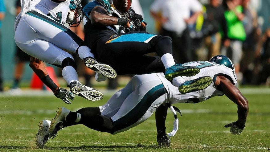 Philadelphia Eagles' Cary Williams, left, and Jaylen Watkins, right, break up a pass intended for Jacksonville Jaguars' Allen Hurns during the second half of an NFL football game, Sunday, Sept. 7, 2014, in Philadelphia. (AP Photo/Michael Perez)